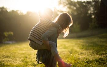 auf einer grünen Wiese: ein Mädchen trägt einen kleineren Jungen auf ihrem Rücken