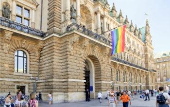 Frontseite des Hamburger Rathauses mit Regenbogenflagge