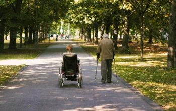 älteres Paar spaziert in einem Park, die Frau sitzt im Rollstuhl, der Mann nutzt Gehhilfen