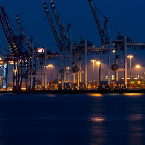 Kräne im Hamburger Hafen bei Nacht, davor ein Containerschiff
