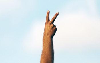 eine Hand fomt mit Zeige- und Mittelfinger das Peace-Zeichen, im Hintergrund ist blauer Himmel