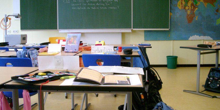 Innenansicht eines Klassenzimmers mit Tischen und einer Tafel im Hintergrund