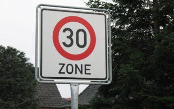 """ein Verkehrsschild mit der Aufschrift """"30 Zone"""", im Hintergrund Bäume"""