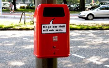 """ein roter Mülleimer mit der Aufschrift """"Möge der Müll mit mir sein"""" an einer Straße in Hamburg"""