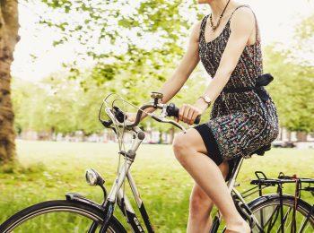Teilansicht einer Radfahrerin, im Hintergrund ein Baum und eine Wiese
