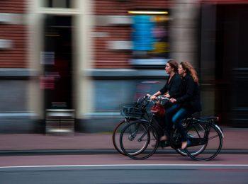 zwei Radfahrerinnen, die auf einem roten Radfahrstreifen nebeneinander fahren