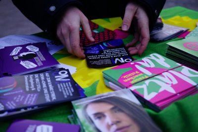 Bild von einem Infostand-Tisch mit (grünen) Flyern zu Feminismus. Ein Flyer, der zum 8.März-Streik aufruft, wird gerade gegriffen.